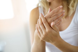 putting moisturizer dry hands